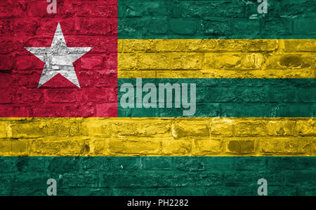 Flag of Togo over an old brick wall background, surface - Stock Photo