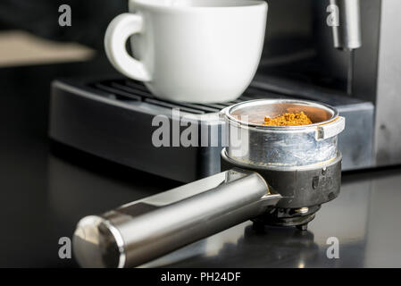 Making a cup of espresso coffee with a close up view of freshly ground coffee beans in the metal measure of a coffee machine with a view to the cup in - Stock Photo