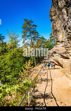 Hikers along the trail to Pravčická brána in Bohemian Switzerland, a picturesque region in the north-western Czech Republic. - Stock Photo