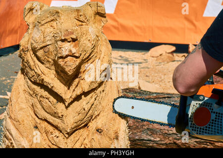 Experienced carpenter making a big wooden bear sculpture with a chainsaw during a local competition close-up - Stock Photo