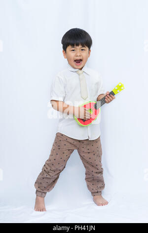 Cute Asian boy holding guitar on white background, portrait boy Open your mouth, - Stock Photo