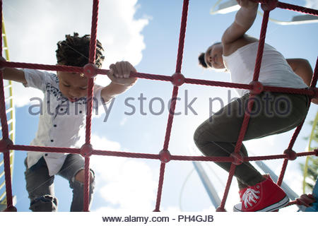 Siblings playing on climbing frame at park - Stock Photo