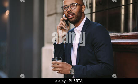 Portrait of handsome young businessman making a phone call while sitting outdoors with a coffee. Man in business suit talking over cell phone. - Stock Photo