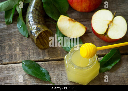 Background Rosh hashanah (Jewish New Year). Traditional holiday symbols - shofar, honey and apple on a kitchen wooden table. - Stock Photo