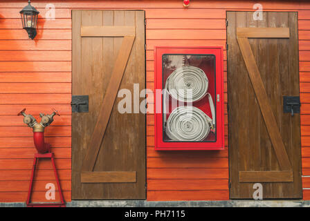 Fire hose in red cabinet hanging on orange wooden wall. Fire emergency equipment box for safety and security system. Fire safety pump. Deluge system o - Stock Photo