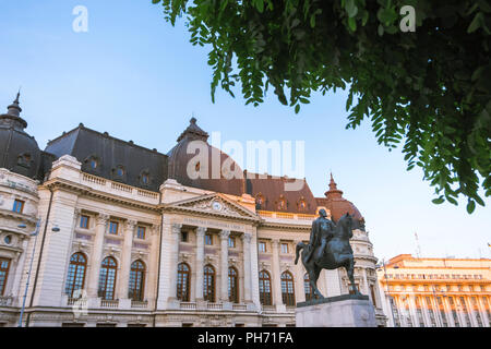 The Central University Library in Bucharest and the statue of King Carol I of Romania in sunset light. - Stock Photo