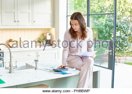 Mid adult woman doing paperwork on kitchen counter. - Stock Photo