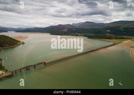 An aerial drone view of the railway viaduct bridge over the Mawddach estuary at Barmouth (Y Bermo / Abermaw in welsh) - a small welsh town and seaside resort , Gwynedd, Snowdonia National Park, North Wales UK (made by a CCA licenced and insured drone operator) - Stock Photo
