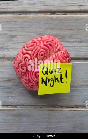 Quiz night label stuck on a brain - Stock Photo