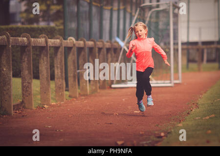 Young girl aged 5-7 running on athletic race track - Stock Photo