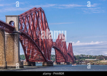 Queensferry, Scotland, UK - June 14, 2012: Red Forth Bridge end upon North Queensferry with old battery fort. Blue sky and gray water. - Stock Photo