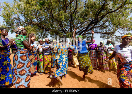 Members of a women's microfinance cooperative welcoming a visitor with dances in Northern Togo, West Africa, Africa - Stock Photo