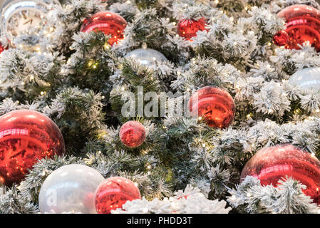 red and white Christmas tree balls with snow-covered fir branches - Stock Photo