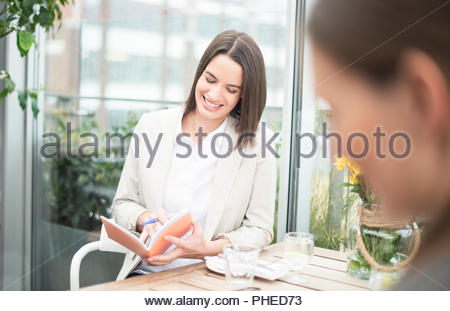 Businesspeople talking during restaurant meeting - Stock Photo