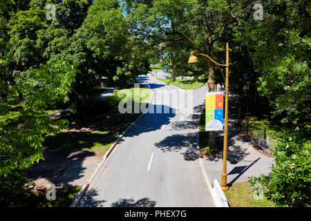 Road junction, lamp post and the banner of Jean Drapeau Park (parc jean drapeau) on Saint Helen's island in Montreal, Quebec, Canada. - Stock Photo