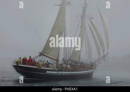 Two masted Schooner with sails on portside tack sails through fog - Stock Photo