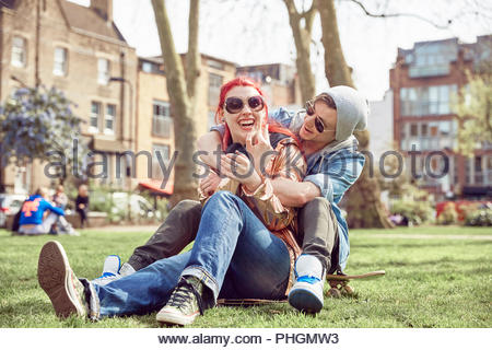 Teenage couple sitting together at park - Stock Photo