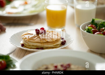 Close up of tasty pancakes served with syrup and berries - Stock Photo