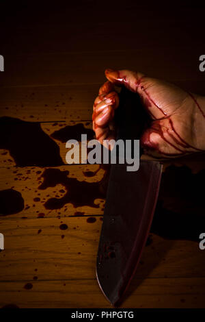 Suicide, murder or crime scene. Hand of a dead person soaked in blood holding a knife on the floor. - Stock Photo