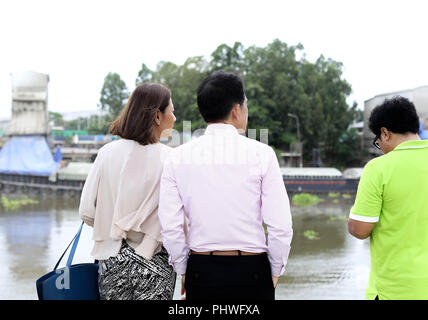Business couple standing and looking at construction site - Stock Photo