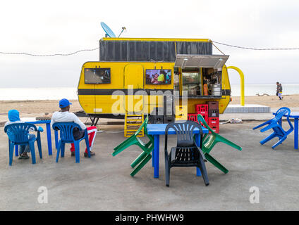 Angolan people watching television in a bar on miragens beach, Namibe Province, Namibe, Angola - Stock Photo