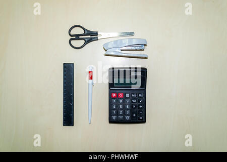 A set of office tools consisting of a calculator, pen, stapler, ruler and scissors lying on a light colored wooden table - Stock Photo