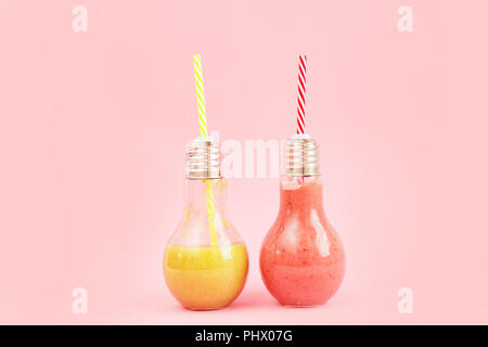 Two lamp- shaped jars with fruit smoothies isolated on pink background. - Stock Photo