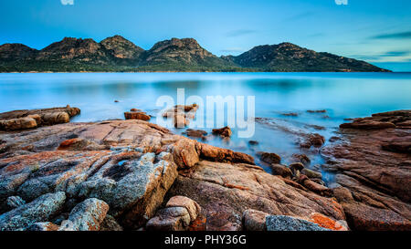 The Hazards in Freycinet National Park at dusk, viewed from Coles Bay in Tasmania, Australia, with orange lichen on granite rocks in the foreground. - Stock Photo
