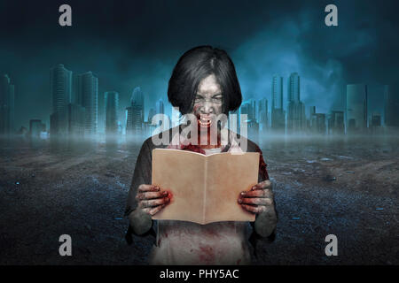 Scary zombie man with dirty face reading the book. Halloween concept - Stock Photo