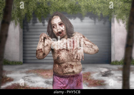 Terrible zombie man with wound on his body haunting abandoned city - Stock Photo