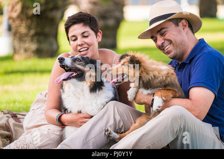 couple of friends in love play and stay well in outdoor leisure activity with their two dogs border collie and shetland. pet and puppy therapy for you - Stock Photo