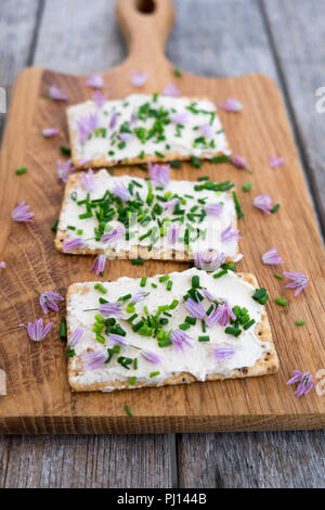 Dairy and lactose-free vegan cream cheese spread made from cashew and macadamia nuts on crackers with fresh chopped chives and edible chive flowers on - Stock Photo