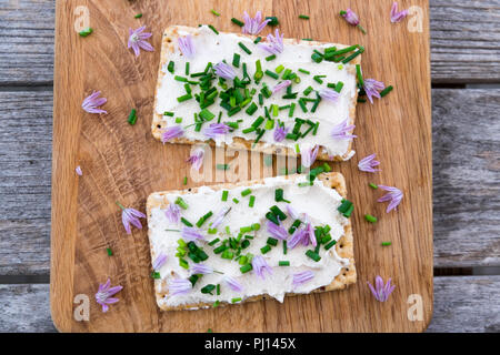 Two dairy and lactose-free vegan cream cheese spread made from cashew and macadamia nuts on crackers with fresh chopped chives and edible chive flower - Stock Photo