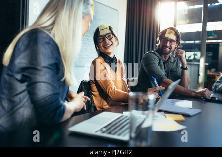 Smiling asian woman with sticky note on her forehead sitting with colleagues in meeting. Diverse business team having a brainstorming meeting in board - Stock Photo