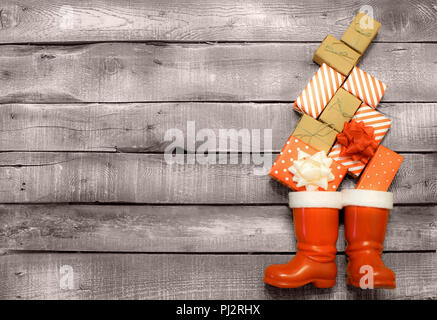 Christmas background - red and brown gifts fall down in Santas or Saint Nicholas boots on grey rustic wooden background - Stock Photo