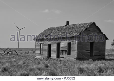 Old dilapidated cabin on the Oklahoma prairie with a new windmill in the background - Stock Photo