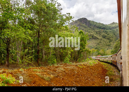 Thailand train on the way to Hell Fire Pass from River Kwai Bridge. The train is running through jungle and river area. - Stock Photo