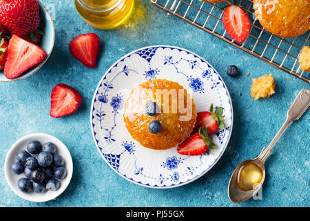 Muffin, cupcake with fresh berries on a plate. Blue background. Top view. - Stock Photo