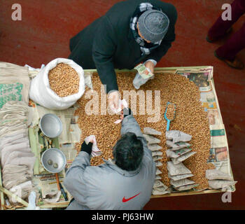Looking down on a street vendor selling hot peanuts and pistachio nuts from a stall in Turkey. - Stock Photo