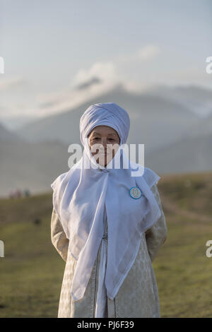 Cholpon-Ata Hippodrome, Kyrgystan. 3rd September 2018. Cholpon-Ata, Indonesia. 3rd Sept 2018. Portrait of Kyrgyz old woman in traditional clothing in front of the Tian Shan mountain landscape on 3 September 2018 on the World Nomad Games in Kyrgyzstan, ethno village Kyrchyn gorge, Cholpon-Ata, Issyk-Kul region Credit: Henri Martin/Alamy Live News - Stock Photo