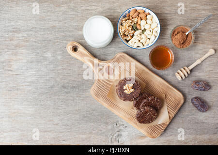 Raw vegan paleo style cookies, made with nuts, coconut oil, honey and dates, selective focus on the walnut on the cookie, top view - Stock Photo