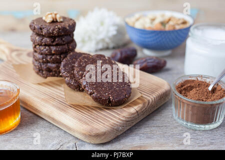 Raw vegan paleo style cookies, made with nuts, coconut oil, honey and dates, selective focus on the nearest cookie - Stock Photo