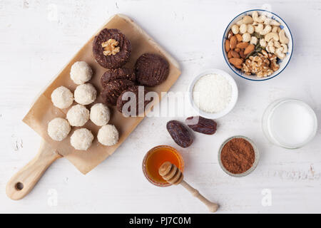 Raw vegan paleo style cookies, selection, made with nuts, coconut oil, honey and dates, top view, selective focus on walnut - Stock Photo