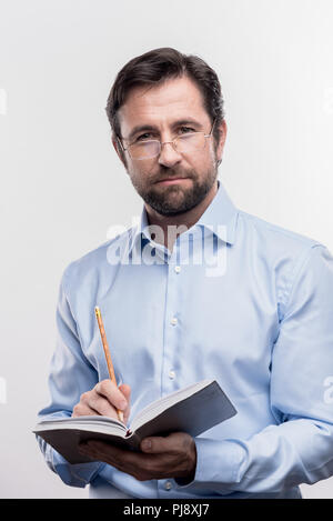 Serious bearded mature man wearing glasses holding pencil making notes - Stock Photo