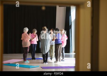 Serene active seniors practicing yoga in circle - Stock Photo