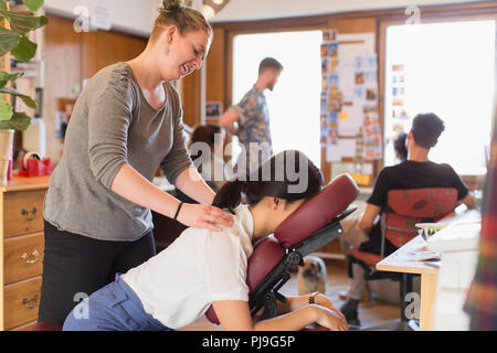 Creative businesswoman receiving massage from masseuse in office - Stock Photo