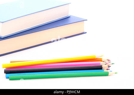 back to school, minimal background, pile of colored pencils and books on the white desk - Stock Photo