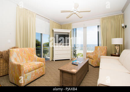 A tastefully decorated living room with a patio door overlooking the ocean. - Stock Photo