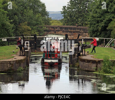 """The narrow boat """"Tufted Duck"""" is entering the 2nd lock of a long flight of locks to start the descent down to Wigan on the Leeds and Liverpool canal. - Stock Photo"""