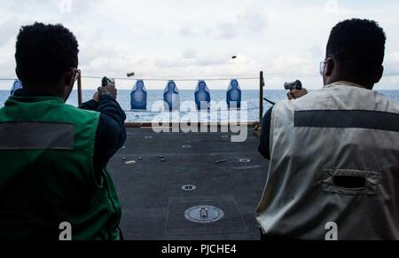 WATERS SOUTH OF JAPAN (July 22, 2018)  Logistics Specialist Seaman Peter Lawson, left, from Atlanta, and Electrician's Mate 3rd Class Tyrone Tyrone, from Stockton, California, fire 9mm pistols during a small arms qualification aboard the Navy's forward-deployed aircraft carrier, USS Ronald Reagan (CVN 76). Ronald Reagan, the flagship of Carrier Strike Group 5, provides a combat-ready force that protects and defends the collective maritime interests of its allies and partners in the Indo-Pacific region. - Stock Photo